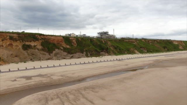 vidéos et rushes de drone aerial showing coastal erosion at cliffs at bacton norfolk with bacton gas terminal perched close to edge of cliff - érodé
