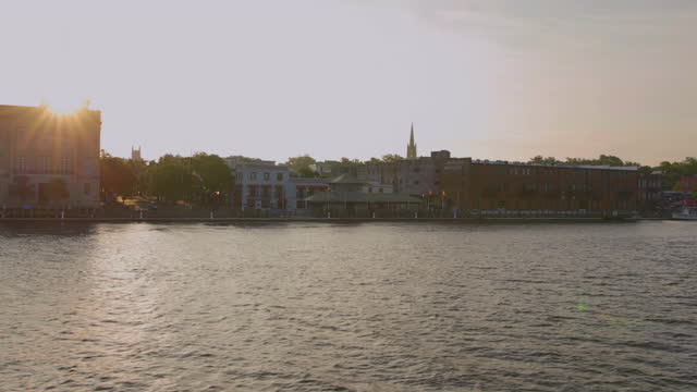 vídeos de stock, filmes e b-roll de drone aerial side pov past alton lennon federal building and riverwalk on cape fear river waterfront in downtown wilmington at sunrise - wilmington carolina do norte