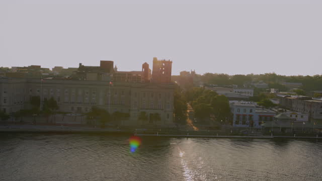 vídeos de stock, filmes e b-roll de drone aerial side pov past riverwalk and alton lennon federal building on cape fear river waterfront in downtown wilmington at sunrise - wilmington carolina do norte