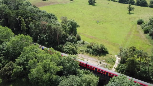 drone aerial south west train going along the guildford to london rail line - activity stock videos & royalty-free footage