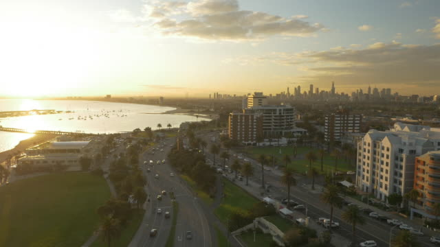 Drone aerial sunset looking north west over St Kilda Esplanade to Melbourne CBD skyline pan and pull back over St Kilda Harbour and Port Phillip Bay