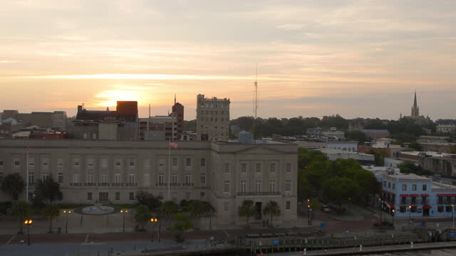 vídeos de stock, filmes e b-roll de drone aerial toward alton lennon federal building on downtown wilmington waterfront on cape fear river at sunrise - wilmington carolina do norte