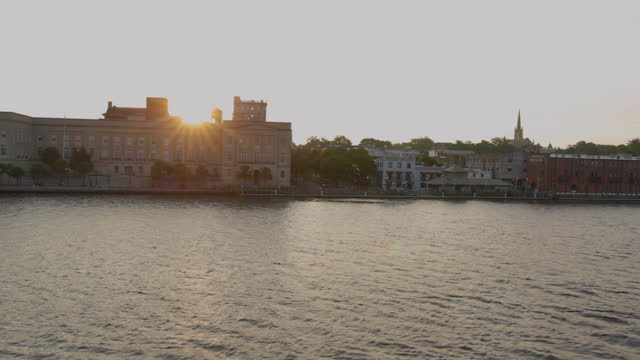 vídeos de stock, filmes e b-roll de drone aerial pov toward alton lennon federal building on downtown wilmington waterfront on cape fear river at sunrise - wilmington carolina do norte