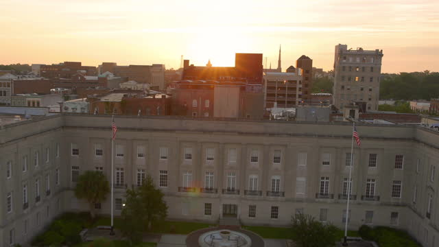 vídeos de stock, filmes e b-roll de drone aerial pov toward and over alton lennon federal building on downtown wilmington waterfront on cape fear river at sunrise - wilmington carolina do norte