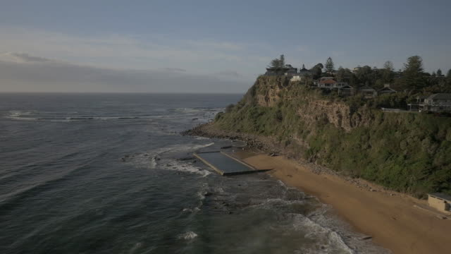 drone aerial tracking along and looking down on Newport beach seeing waters edge and footprints in the sand tilting up to see Bungan Headland and...