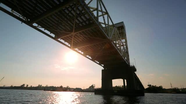 MEDIUM drone AERIAL under Cape Fear Memorial Bridge at sunset