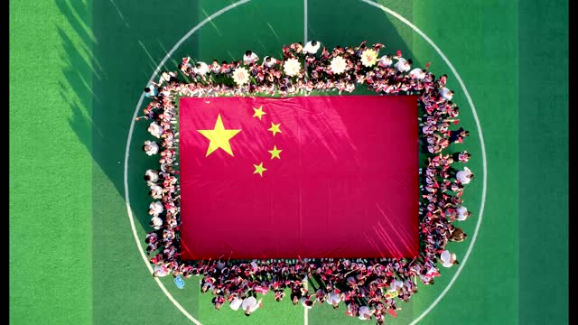 drone aerial video of primary and secondary school students gathering around the chinese national flag in the playground, celebrating national day in... - celebratory event stock videos & royalty-free footage