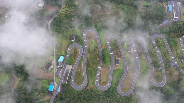 drone aerial video of taiyanghe township's winding mountain road with hairpin turns in fog in enshi city hubei province by costfoto / barcroft... - winding road stock videos & royalty-free footage