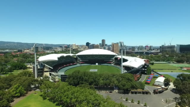 stockvideo's en b-roll-footage met drone aerial view adelaide oval - empty with cricket pitch square covered, adelaide city skyline and adelaide hills in the background, clear blue... - cricketveld