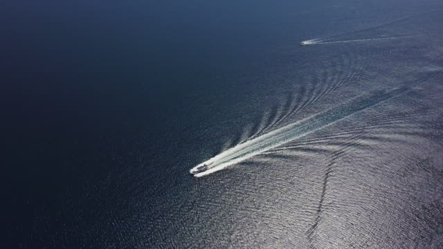 drone aerial view of a boat sailing the sea - small boat stock videos & royalty-free footage