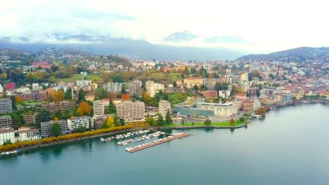 夏の日中にティチーノのルガーノ湖ルガーノ市のドローンの空中ビュー。上からの街の眺め、湖と山々を背景に - ヨーロッパ点の映像素材/bロール