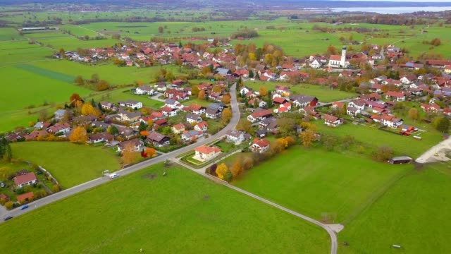 vídeos de stock, filmes e b-roll de vista aérea do zangão da cidade pequena com a vila pequena da exploração agrícola da estrada no lado alemanha do país - aldeia