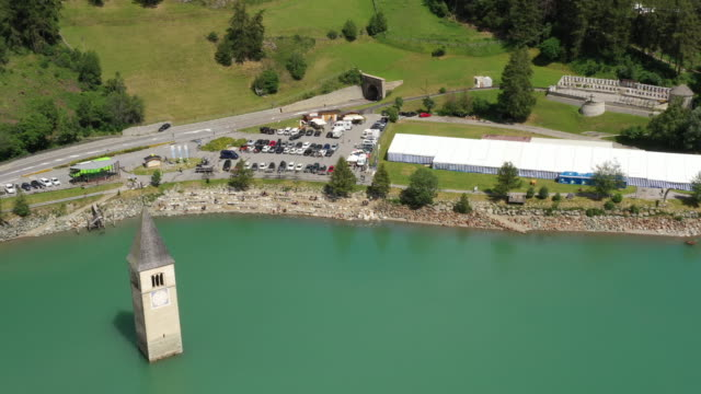 drone aerial view of the old bell tower of the village rising out of the waters lake of resia - lago video stock e b–roll