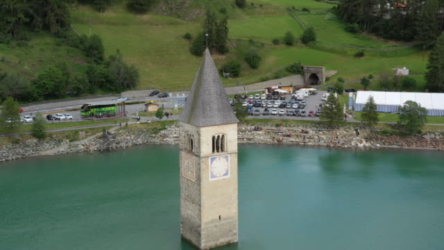 drone aerial view of the old bell tower of the village rising out of the waters lake of resia - monumento video stock e b–roll