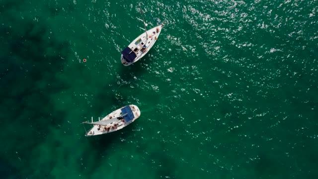 vídeos de stock e filmes b-roll de drone aerial view of tourists enjoying a paradise luxury yacht trip around tenerife, canary islands, spain, atlantic, europe - embarcação de lazer