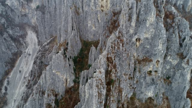 drone: aerial view of very high jagged rock formations like needles, climbing destination, extreme sports, high situated caves, national park, close up, travel destination - granite rock stock videos & royalty-free footage
