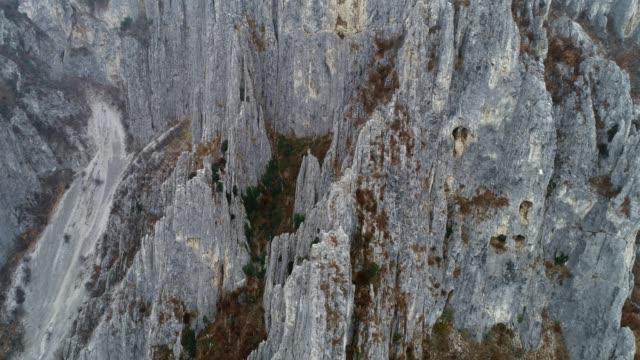 stockvideo's en b-roll-footage met drone: luchtfoto van zeer hoge gekartelde rotsformaties zoals naalden, klimmen bestemming, extreme sporten, hoog gelegen grotten, nationaal park, close-up, reizen bestemming - graniet