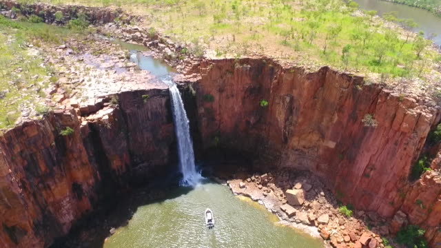 drone aerial - waterfall flowing into the gorge, drone moves in towards and over the waterfall / creek flowing into the waterfall / distant views of... - outback stock videos & royalty-free footage