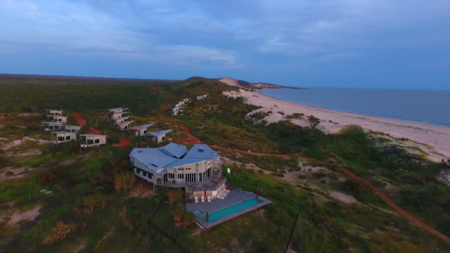 drone aerials, 360 degree, over the sand dunes and vegetation / 'berkeley river lodge' lodges scattered over the headland, billabong, with trees... - lido stock videos & royalty-free footage