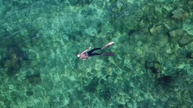 drone aerials of boat moored by small hut out at sea man snorkelling in clear waters near boat on 24th september 2017 in tripoli libya - hut stock videos & royalty-free footage