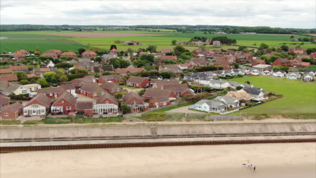 vidéos et rushes de drone aerials of houses and sea wall along norfolk coast at bacton and walcott, an area that suffers from coastal erosion - érodé