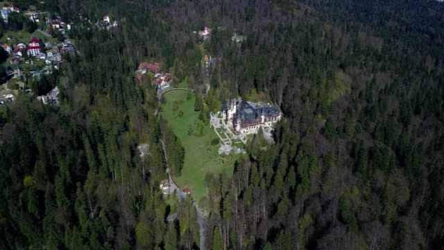 A drone approaches and flies over Peles Castle in Sinaia Prahova Romania