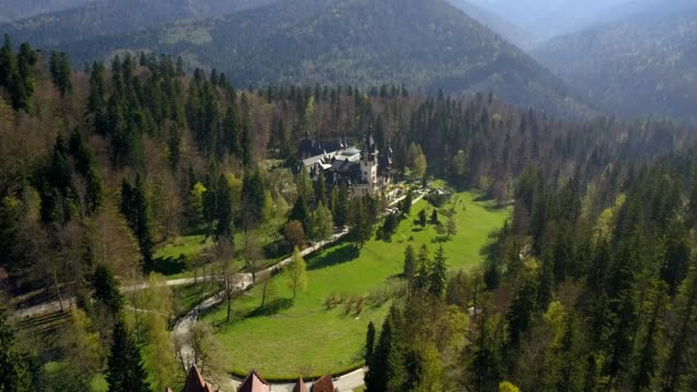 a drone approaches peles castle in sinaia prahova romania - transilvania video stock e b–roll