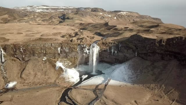 a drone approaches seljalandsfoss waterfall in iceland - seljalandsfoss waterfall stock videos and b-roll footage