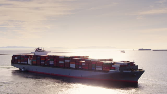drone approaching cargo ship arriving in port - ship stock videos and b-roll footage