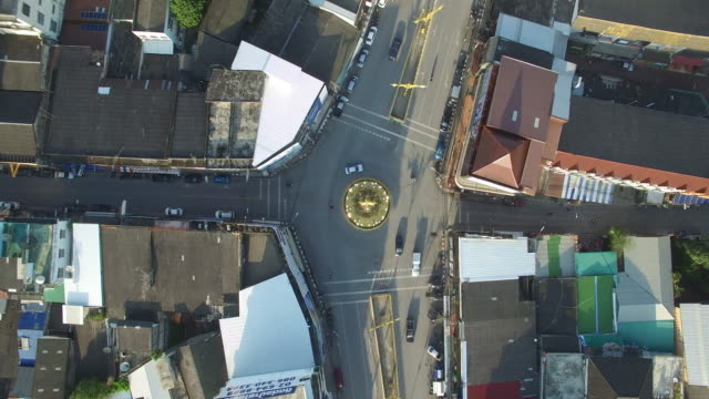 drone ascend over the golden clock tower sitting in the middle of a roundabout on baanpa pragarn road in central chiang rai - clock tower stock videos & royalty-free footage