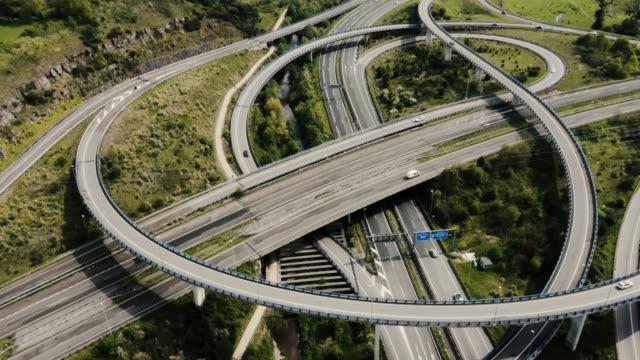 drohne steigt und dreht schnell über große autobahn - straßenüberführung stock-videos und b-roll-filmmaterial