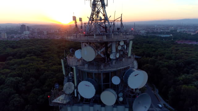 drone ascending near radio tower at sunset revealing beautiful cityscape - mast stock videos & royalty-free footage