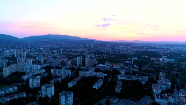 vidéos et rushes de drone tir ascendant révélant le coucher de soleil rose pourpre sur la ville - être debout