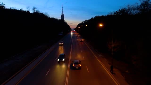 vídeos de stock, filmes e b-roll de um robô é à noite, voando baixo sobre carros no trânsito da cidade - bulgária