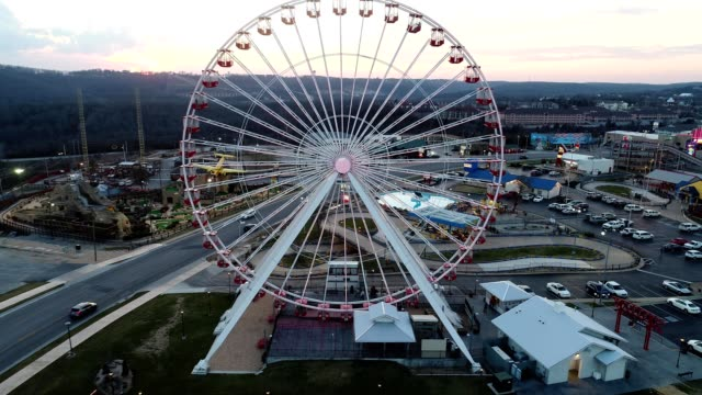 vídeos de stock e filmes b-roll de a drone backs away from a ferris wheel in branson missouri - missouri