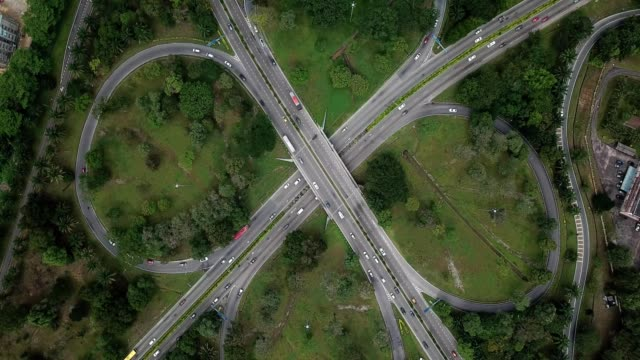 a drone birdseye ascends over a 4 way expressway in johor bahru malaysia - malaysia stock videos and b-roll footage