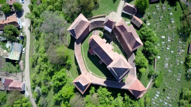 a drone birdseye orbits the fortified church of viscri in județul brașov romania - transilvania video stock e b–roll