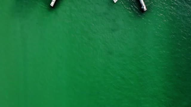 vídeos de stock, filmes e b-roll de a drone birdseye views a boat passing under a drawbridge in sarasota florida - drawbridge