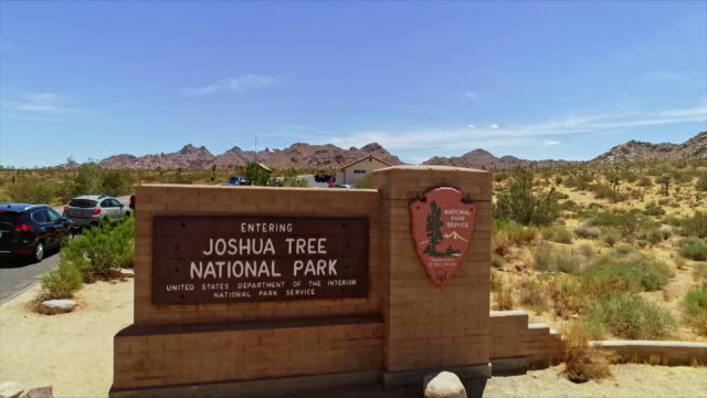 ws drone booms up from national park service entrance sign at guard gate to high angle view of cars waiting to enter joshua tree national park - joshua tree national park stock videos & royalty-free footage