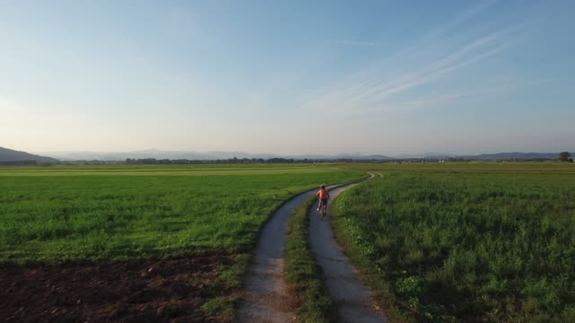 uhd drone: boy riding a bicycle at sunset - mountain biking stock videos & royalty-free footage
