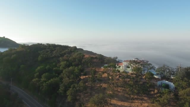 stockvideo's en b-roll-footage met drone camera approaches the cliff of the canyon with house, road and forest. around the thick morning clouds (malibu canyon, monte nido, california, usa) - bergrug