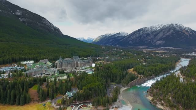 vídeos de stock e filmes b-roll de drone camera captured the beautiful nature that surrounds a huge hotel on the banks of bow river (banff, alberta, canada) - bandeira do canadá