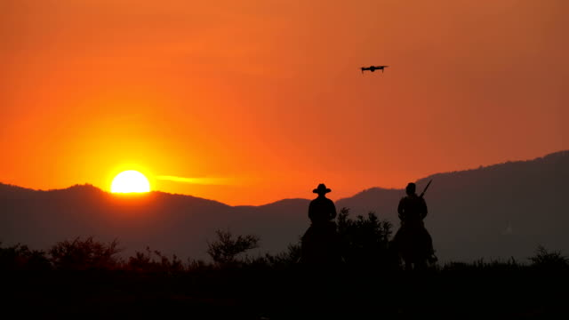 drone camera flying to shooting shot of soldier and cowboy riding horses walking into the sunset - domination stock videos & royalty-free footage