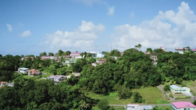 drone camera is gradually approaching the horizon with clouds over a town with dense vegetation (saint lucia) - st. lucia stock videos & royalty-free footage