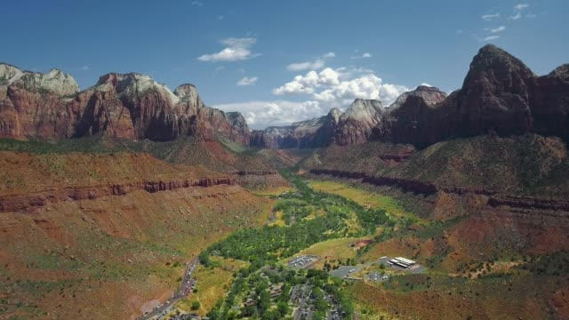 drone camera moves over a settlement and green forest on a dried riverbed in a canyon (zion national park, utah, usa) - zion national park stock videos & royalty-free footage