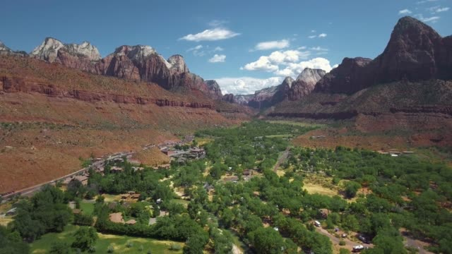 drone camera moves over the settlement near the highway at the bottom of the canyon (zion national park, utah, usa) - gebäudefries stock-videos und b-roll-filmmaterial