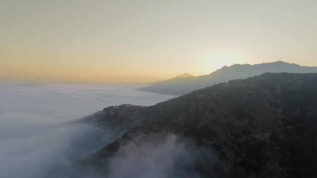 stockvideo's en b-roll-footage met drone camera moves smoothly in the foggy dawn over the canyon (malibu canyon, calabasas, california, usa) - bergrug