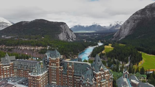 drone captured a hotel with mountains and a forest valley in banff, alberta, canada - ridge stock videos & royalty-free footage