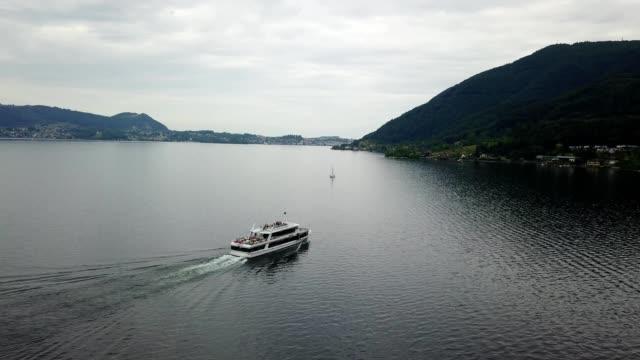 a drone captures a boat on a lake in linz austria - アッパーオーストリア点の映像素材/bロール