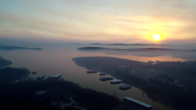 vídeos de stock e filmes b-roll de a drone captures a hazy sunset over table rock lake in branson missouri - missouri